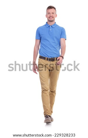 full length picture of a young casual man walking toward the camera and smiling. isolated on a white background - stock photo