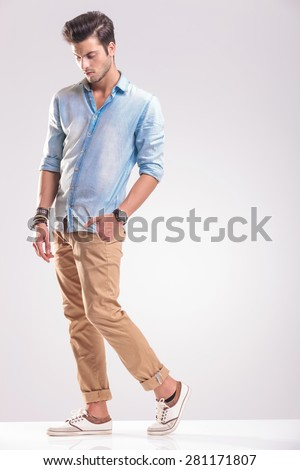 Full length picture of a young casual man walking with his hand in pocket while looking down. - stock photo