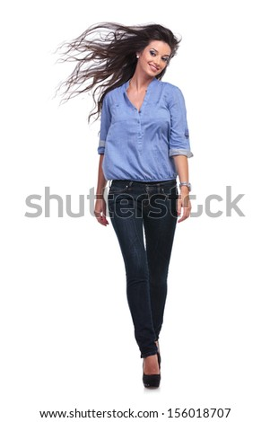 full length picture of a young casual woman walking toward the camera and smiling while looking away. on white background - stock photo