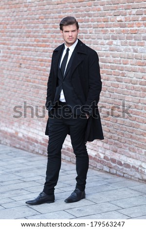 full length picture of an elegant young business man posing on a sidewalk next to a brick wall, with his hands in his pockets and looking into the camera - stock photo