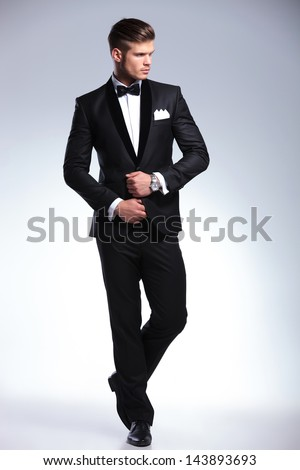 full length picture of an elegant young fashion man adjusting his tuxedo while looking to his side, away from the camera. on gray background - stock photo