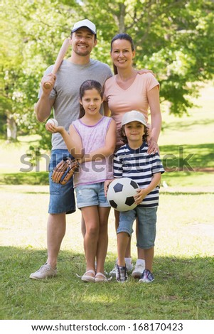 Full length portrait a family of four holding baseball bat and ball in the park - stock photo