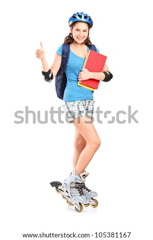 Full length portrait a girlon rollers holding notebooks and giving thumb up isolated against white background - stock photo