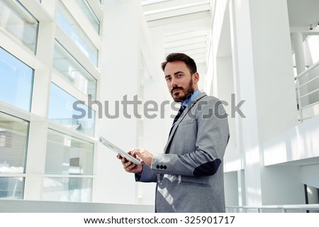 Full length portrait a young smart managing director holding touch pad while standing in big white hallway, handsome confident businessman dressed in luxury suit using touch pad during work break  - stock photo