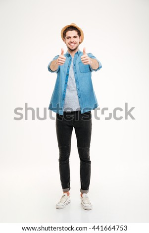 Full length portrait cheerful young man showing thumbs up isolated on a white background - stock photo