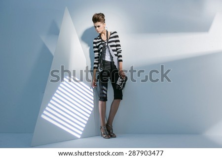 Full length portrait fashion model holding purse standing posing on light background - stock photo