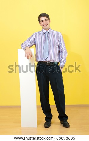 full length portrait of a attractive smiling young businessman leaning on empty sheet against uniform background - stock photo