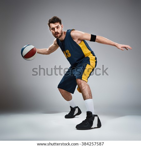 Full length portrait of a basketball player with ball  - stock photo
