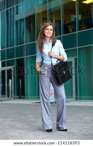 Full length portrait of a beautiful attractive smiling young businesswoman with briefcase, background - stock photo