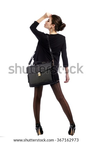 Full length portrait of a beautiful brunette in a business style, in suit and stockings with a briefcase on a gray background studio - stock photo