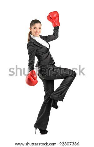 Full length portrait of a beautiful business woman wearing boxing gloves isolated on white background - stock photo