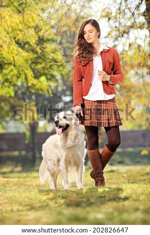 Full length portrait of a beautiful girl walking her dog in park  - stock photo