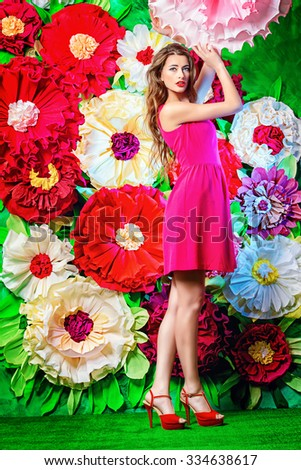 Full length portrait of a beautiful happy young woman posing on a background of bright large flowers. Beauty, fashion. Summer inspiration. - stock photo