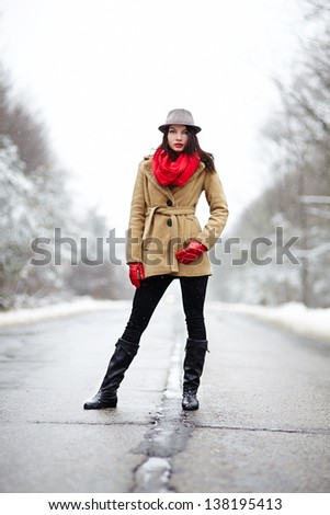 Full length portrait of a beautiful woman posing on a road in the winter - stock photo