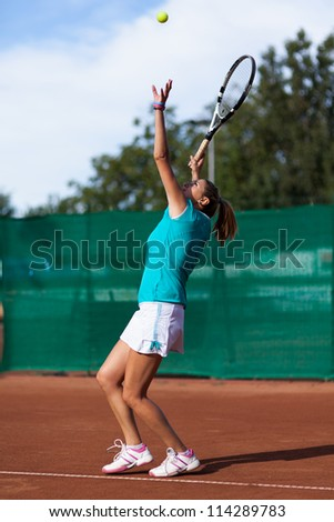 Full length portrait of a beautiful woman tennis player serving a tennis ball - stock photo