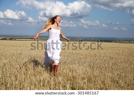 Full length portrait of a beautiful young happy woman in a white dress running through the wheat field - stock photo