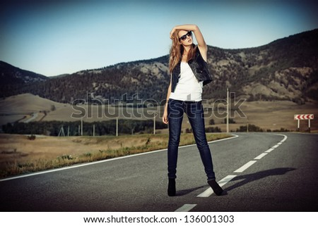 Full length portrait of a beautiful young woman posing on a road over picturesque landscape. - stock photo