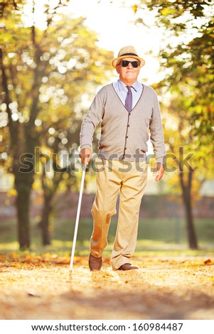 Full length portrait of a blind mature person holding a stick and walking in a park - stock photo