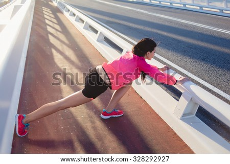 Full length portrait of a brunette female runner dressed in bright sportswear stretching body muscles before start her jog, young athletic woman doing warm up exercise outside in sunny summer evening - stock photo
