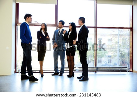 Full length portrait of a business people talking in the office - stock photo