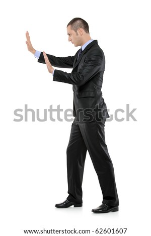 Full length portrait of a businessman pushing something imaginary isolated on white background - stock photo
