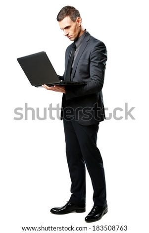 Full-length portrait of a businessman standing and using laptop isolated on a white background - stock photo