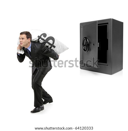Full length portrait of a businessman stealing a money bag from a deposit safe isolated on white background - stock photo