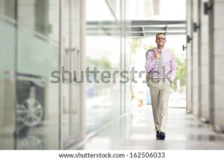 Full-length portrait of a businessman walking in the business centre  - stock photo