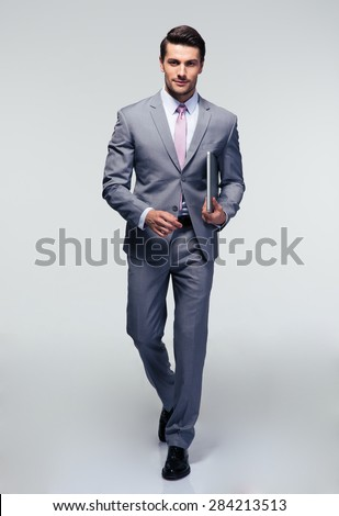 Full length portrait of a businessman walking with latpop over gray background - stock photo