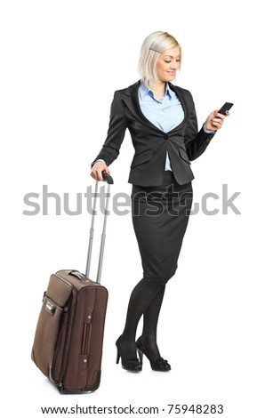 Full length portrait of a businesswoman carrying a suitcase and writing a sms isolated on white background - stock photo