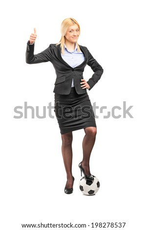 Full length portrait of a businesswoman standing on a football and giving thumb up isolated on white background - stock photo