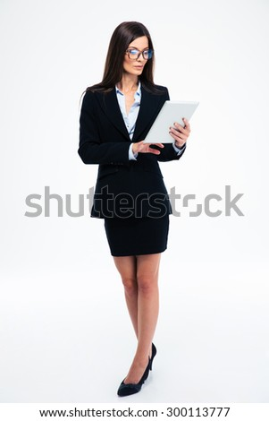 Full length portrait of a businesswoman using tablet computer isolated on a white background - stock photo