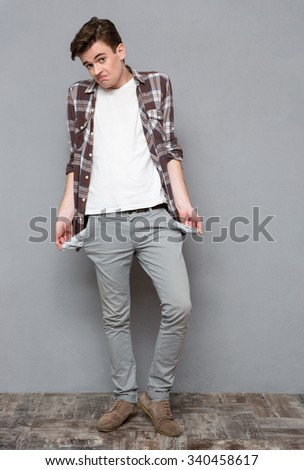 Full length portrait of a casual man exhibiting his empty pockets on gray background - stock photo