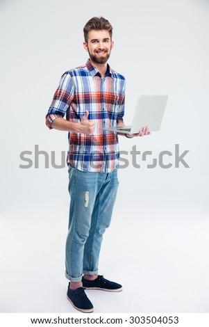 Full length portrait of a casual man standing with laptop and showing thumb up sign isolated on a white background. Looking at camera - stock photo