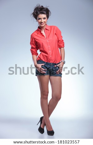 full length portrait of a casual young woman holding her thumbs in the loops of her short jeans and her legs crossed while smiling for the camera. on a gray light studio backgroud - stock photo