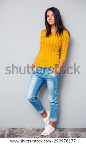 Full length portrait of a casual young woman posing on gray background - stock photo