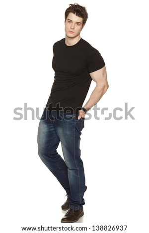 Full length portrait of a casually-dressed young man with his hands in his rear pockets over white background - stock photo