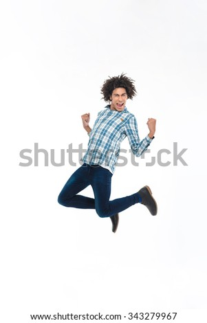 Full length portrait of a cheerful afro american man jumping isolated on a white background  - stock photo