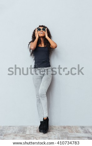 Full length portrait of a cheerful afro american woman posing on gray background - stock photo