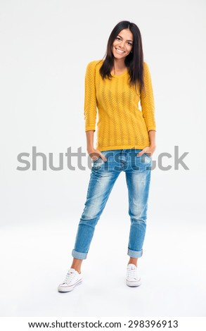 Full length portrait of a cheerful casual woman standing isolated on a white background. Looking at camera - stock photo