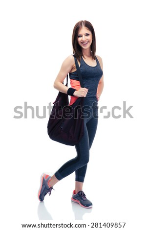 Full length portrait of a cheerful fitness woman standing with bag isolated on a white background and looking at camera - stock photo
