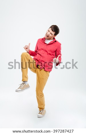 Full length portrait of a cheerful man showing thumbs up isolated on a white background - stock photo