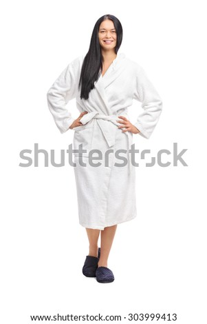 Full length portrait of a cheerful woman in a white bathrobe, looking at the camera and smiling isolated on white background - stock photo