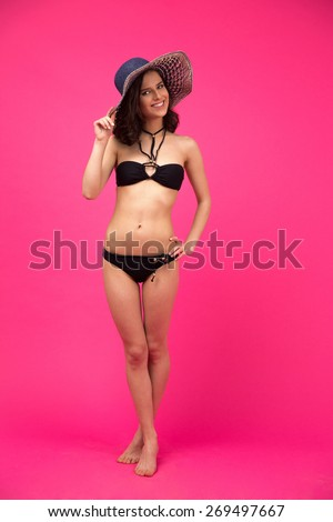 Full length portrait of a cheerful woman in swimsuit over pink background - stock photo