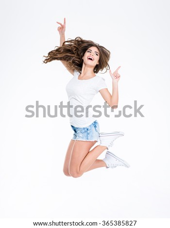 Full length portrait of a cheerful woman jumping isolated on a white background - stock photo