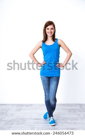 Full length portrait of a cheerful woman standing at studio - stock photo