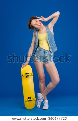 Full length portrait of a cheerful woman standing with skateboard and showing peace sign over blue background - stock photo