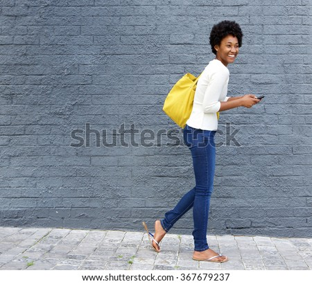 Full length portrait of a cheerful young african woman walking on street with a mobile phone - stock photo