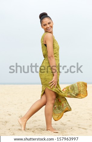 Full length portrait of a cheerful young woman walking at the beach - stock photo