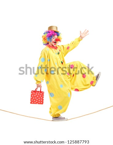 Full length portrait of a clown holding a bag and walking on a rope isolated on white background - stock photo